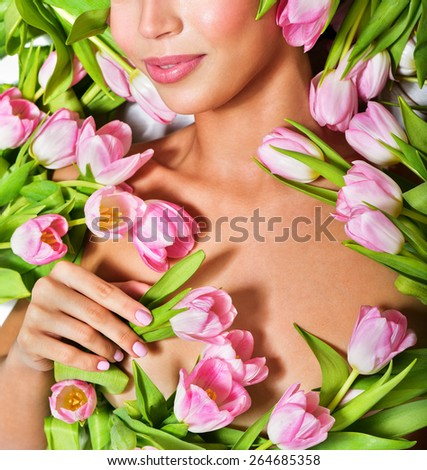 Beautiful woman's face surrounded by pink tulips. Spring Flower. Springtime. Perfect skin