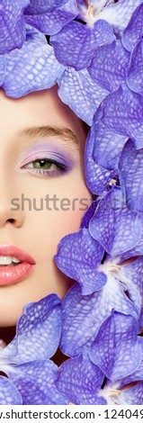 beautiful woman's face, surrounded by purple orchids - stock photo