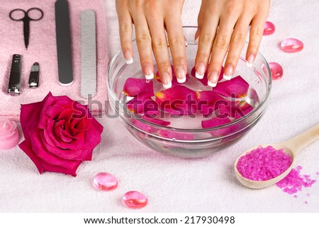Beautiful woman's hands with french manicure in bowl of water with rose petals - stock photo