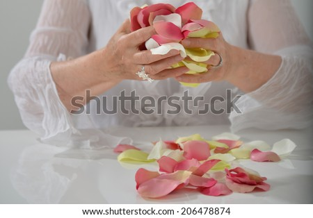 Beautiful woman's hands with yellow and pink petals - stock photo