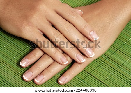 Beautiful woman's nails with perfect french manicure on bright green natural bamboo. Care for female hands - stock photo