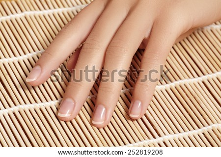 Beautiful woman's nails with perfect french manicure on natural bamboo. Care for female hands  - stock photo