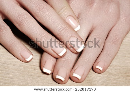 Beautiful woman's nails with perfect french manicure on natural wood background. Care for female hands. Natural look with light nail polish, beauty care.