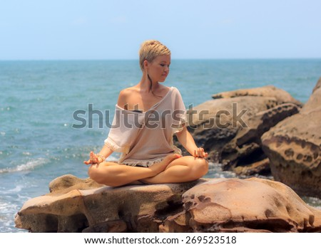 Beautiful woman seated in yoga pose at rocky blue sea background horizontal view - stock photo