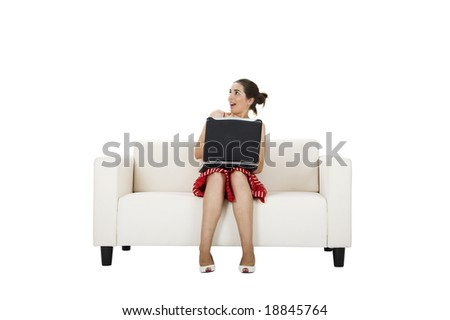 Beautiful woman seated on a couch talking with a laptop with a surprised expression - stock photo