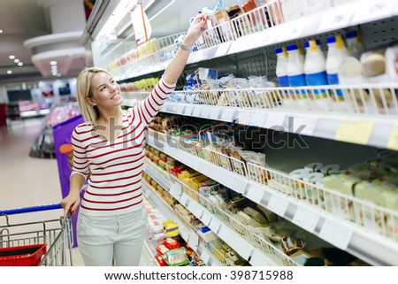 Beautiful woman shopping in supermarket and deciding what to buy - stock photo