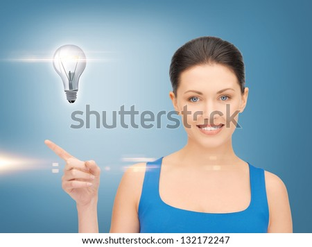beautiful woman showing light bulb on her hand