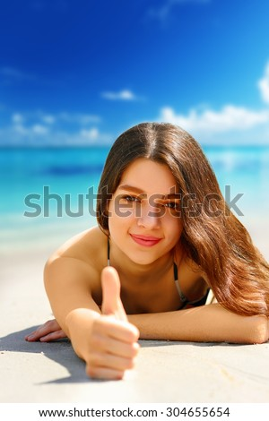 Beautiful  woman showing OK by her finger on the beach - stock photo