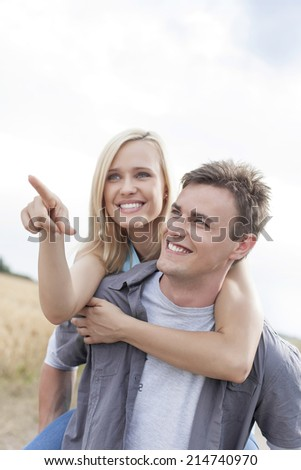 Beautiful woman showing something to man while enjoying piggyback ride at field - stock photo