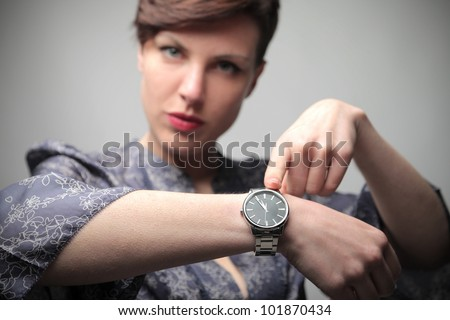 Beautiful woman showing the time on her wrist watch - stock photo