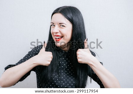 Beautiful woman showing thumbs up. On a gray background. - stock photo