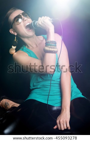 Beautiful woman singer in the spotlight - stock photo