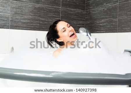 Beautiful woman singing in bath smile, young girl bathing hold with shower head in bathtub jacuzzi with foam