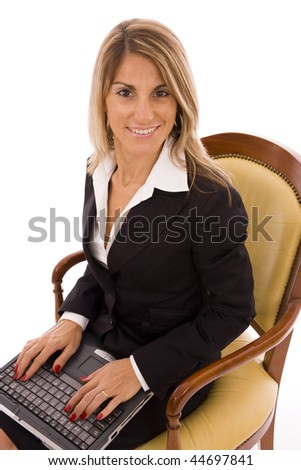Beautiful woman sit on an armchair typing on a laptop