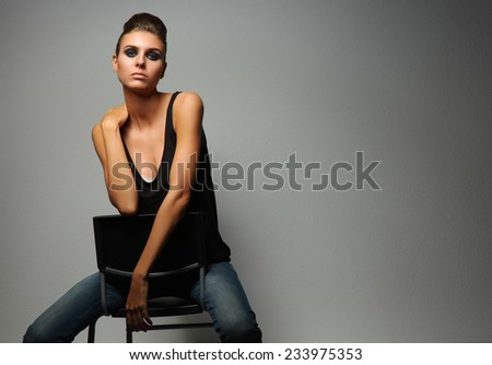 Beautiful woman  sitting  a chair, isolated on gray background
