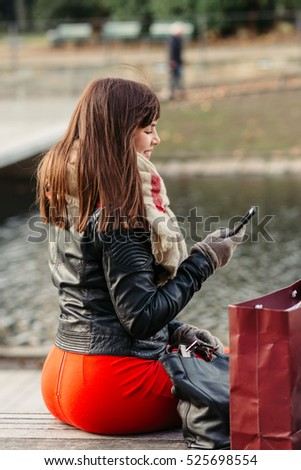 beautiful woman sitting after shopping and talking on smart phone outdoor