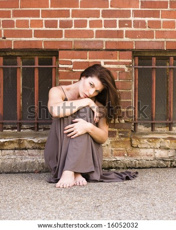 Beautiful woman sitting against a brick wall