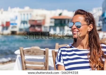 Beautiful woman sitting at a seaside cafe - stock photo