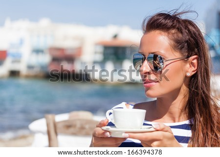 Beautiful woman sitting at a seaside cafe and drinks a coffee - stock photo