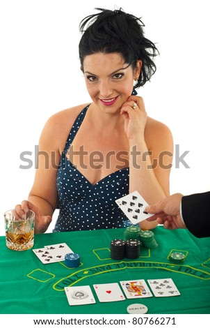 Beautiful woman sitting at casino table and receiving card from dealer hand against white background
