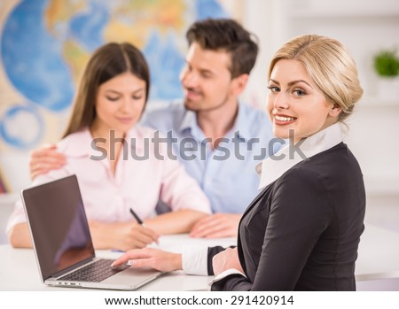 Beautiful woman sitting at office with clients and proposing hot tours to them.
