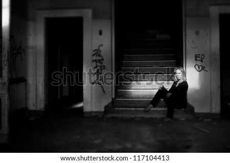 Beautiful  woman sitting at the bottom of a staricase in derelict abandoned building