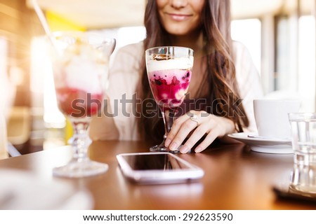 Beautiful woman sitting at the table in cafe - stock photo