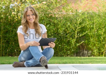 Beautiful woman sitting by a pool holding a tablet