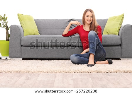 Beautiful woman sitting by a sofa on the floor isolated on white background - stock photo