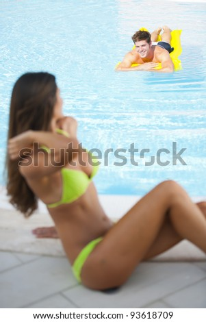 Beautiful woman sitting by pool, man on air mattress