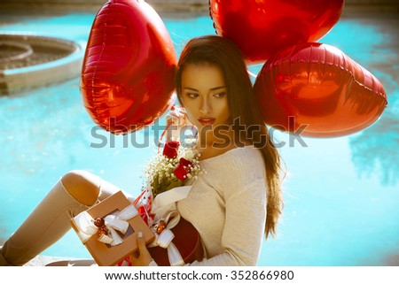 beautiful woman sitting by the pool and holding red heart balloons with gifts boxes and bouquet of flowers. Colorfull image. Woman by the pool. Valentines day . horizontal shot, outdoors
