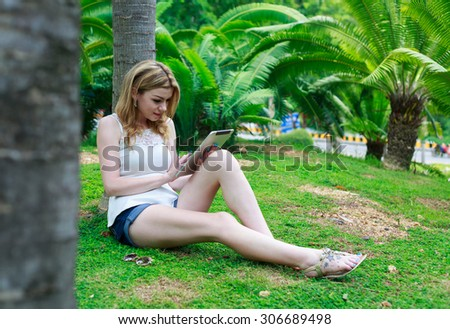 Beautiful Woman Sitting Down At The Park Talking On Mobile Phone - stock photo