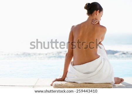 beautiful woman sitting from the back on beach - stock photo