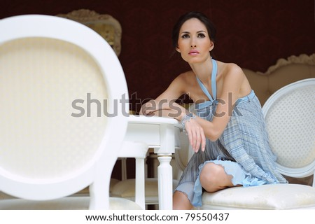 beautiful woman sitting in a chair in the house - stock photo