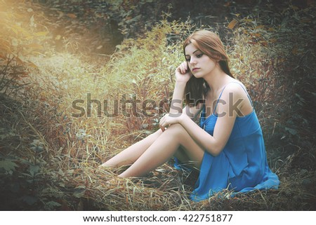 Beautiful Woman sitting in a field close-up portrait