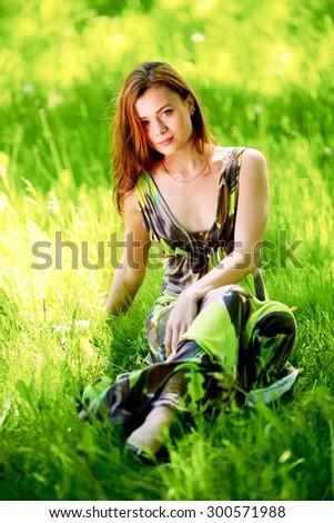 Beautiful woman sitting in a green field enjoying the summer sunlight - stock photo