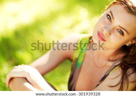 Beautiful woman sitting in a green field enjoying the summer sunlight - stock photo
