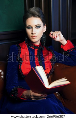 beautiful woman sitting in a leather chair in retro dress reading a book