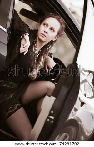Beautiful woman sitting in a sports car - stock photo
