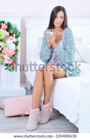 Beautiful woman sitting in bed with a cup of morning coffee - stock photo