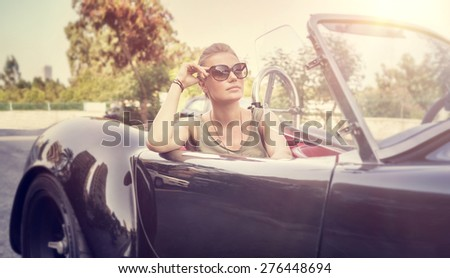 Beautiful woman sitting in cabriolet, sexy female enjoying trip on luxury modern car with open roof, fashionable lifestyle concept - stock photo
