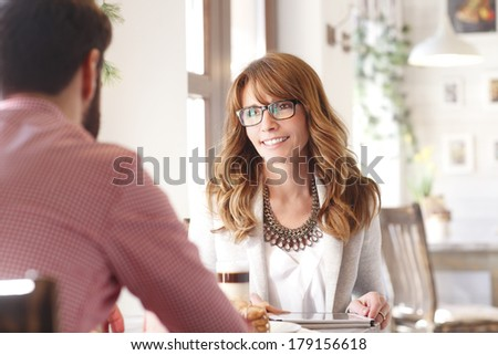 Beautiful woman sitting in coffee shop and chatting.