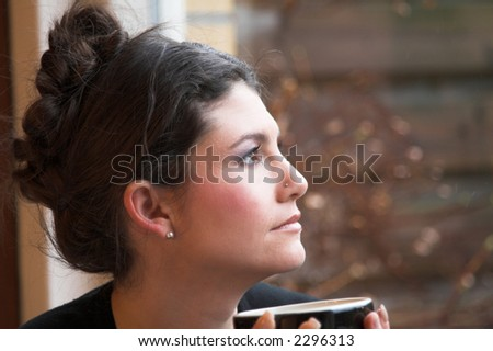 beautiful woman sitting in front of the window staring out - stock photo