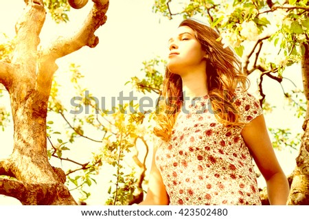 Beautiful woman sitting in the tree and  enjoying the smell of flowering spring garden - stock photo
