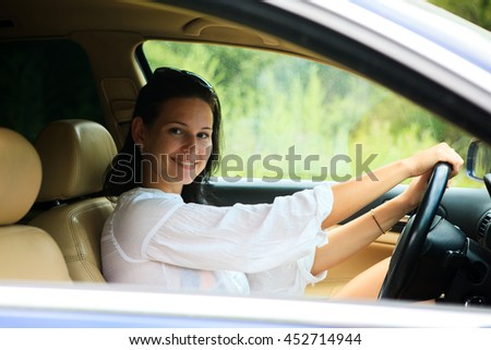 Beautiful Woman sitting inside the car in a white shirt - stock photo
