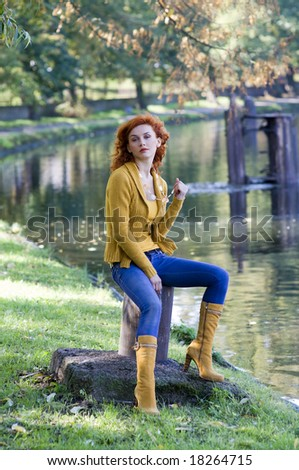 beautiful woman sitting near river in yellow casual autumn dress