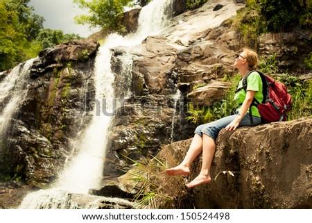 Beautiful  woman sitting near the waterfall enjoying the sun - stock photo