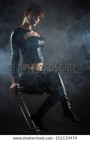 beautiful woman sitting on a bar stool in profile face - stock photo