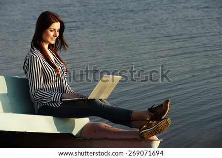 Beautiful woman sitting on a beach and using a laptop - stock photo