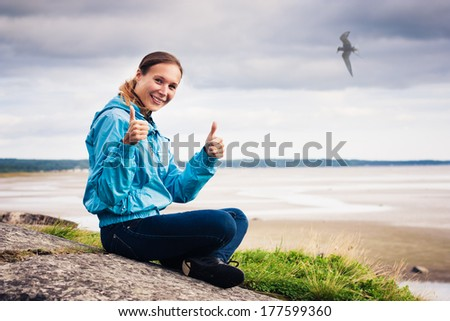 Beautiful woman sitting on a cliff over the sea and meditating - stock photo